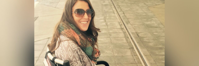 Nicole smiling, sitting outdoors in her portable wheelchair.