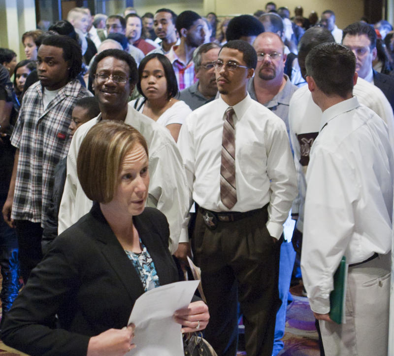 Job seekers who arrived early to a job fair in Omaha, Neb., Wednesday, April 6, 2011, wait to be admitted. Fewer people applied for unemployment benefits last week, a sign that layoffs are dropping and employers may be hiring more workers.  (AP Photo/Nati Harnik)