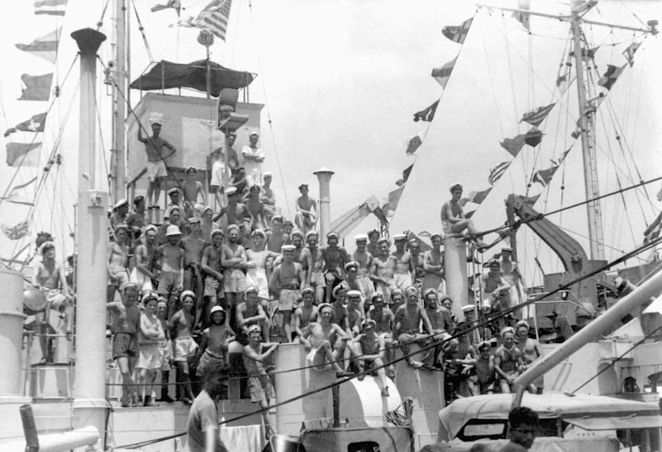 <p>Officers aboard the Tank Landing Ship HMS LST 538 cheer and celebrate as signal flags are hoisted upon word from Delhi announcing the end of hostilities in Europe, off Ramree Island, Burma.</p>