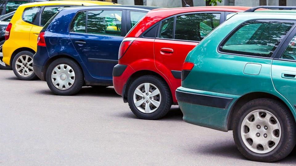 several multicolored cars parked diagonally at parking lot in the street.