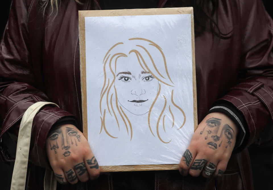 A demonstrator holds a caricature of murder victim Sarah Everard near New Scotland Yard in London, Sunday, March 14, 2021 during a protest her abduction and murder and the subsequent handling by the police of a vigil honoring the victim. London's Metropolitan Police force was under heavy pressure Sunday to explain its actions during a vigil for Sarah Everard whom one of the force's own officers is accused of murdering. (AP Photo/Frank Augstein)