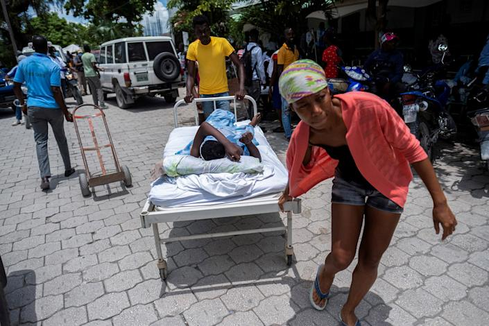 """A woman injured in the earthquake is transported to a hospital in Les Cayes on Aug. 16.<span class=""""copyright"""">Ricardo Arduengo—Reuters</span>"""