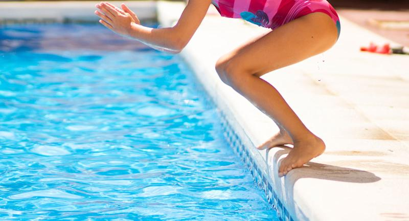 A little girl is seen preparing to dive into a swimming pool.