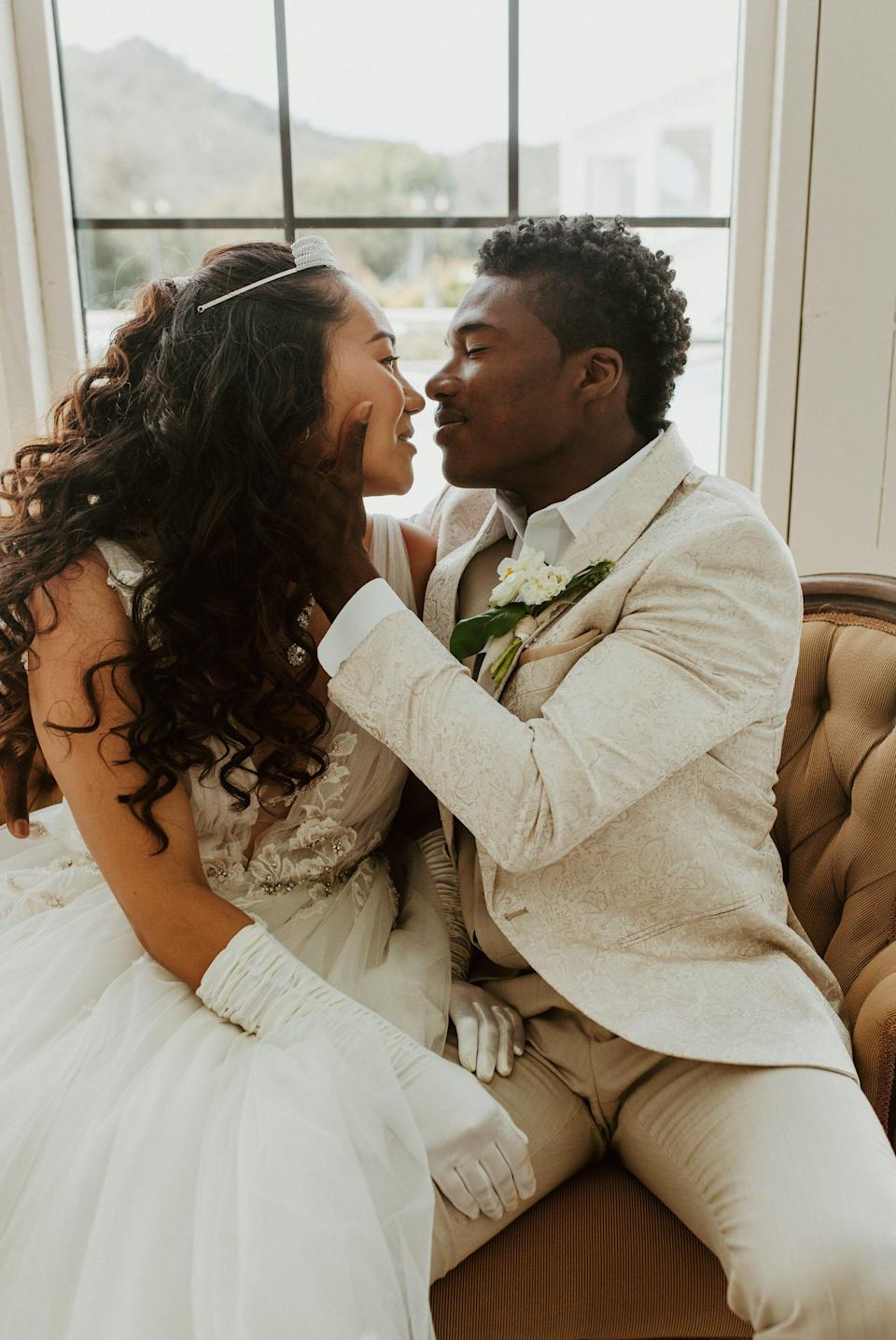 A groom caresses a bride's face as they look at each other and sit on a couch.