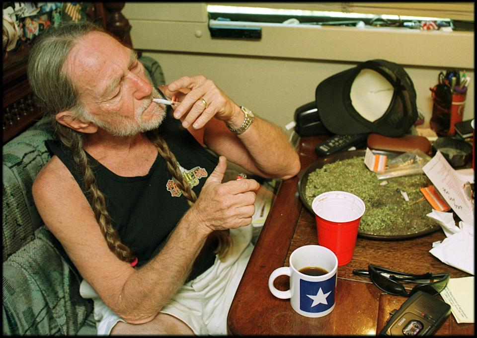 American country singer Willie Nelson takes a drag off a joint while relaxing at his home in Texas, 2000s. A large amount of marijuana is spread out on the table before him (Photo by  Liaison/Getty Images)