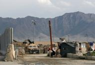 An Afghan National Army (ANA) soldier sits at the gate of Bagram prison, north of Kabul, Afghanistan