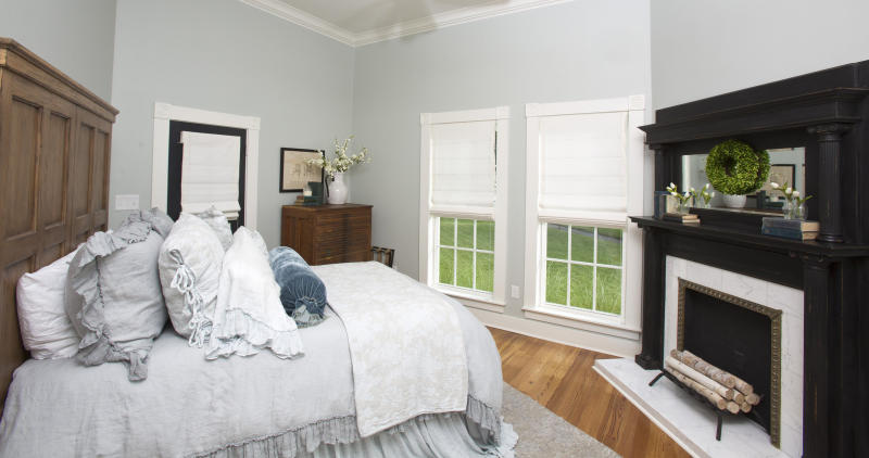 This downstairs bedroom features hardwood floors, cool gray wall paint and a restored fireplace. (Fort Worth Star-Telegram via Getty Images)