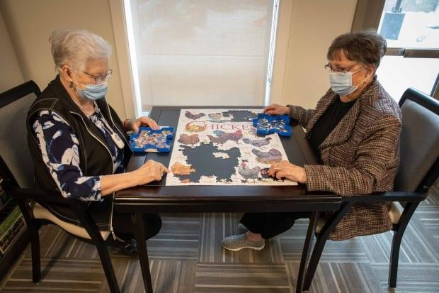 Helen Friesen and Gladys Kram work on a puzzle together in a common area of Harbour Landing Village. The company's CEO said it was important to the mental and physical health of seniors that they weren't 'locked in their rooms' during the pandemic.