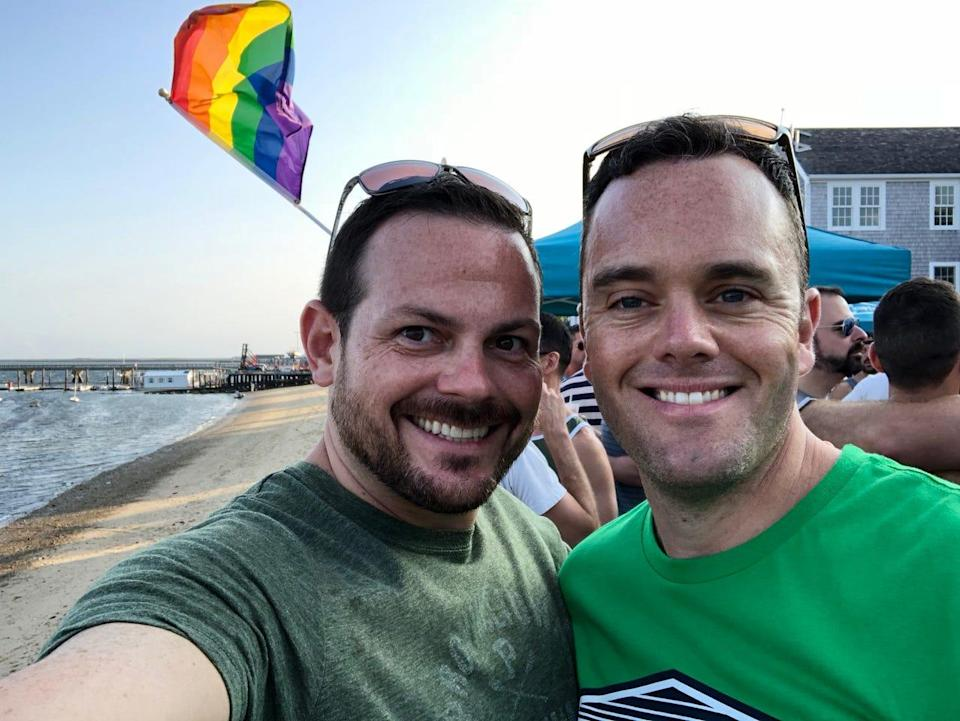 LeeMichael McLean and Bryan Furze pose in front of a Pride flag. During more than five years of harassment, about 30 pieces of mail with homophobic fake names on them were sent to the couple's home in Milton, Massachusetts.