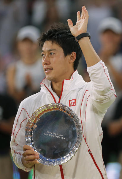 Kei Nishikori from Japan holds his trophy while waving after his Madrid Open tennis tournament final match against Rafael Nadal from Spain in Madrid, Spain, Sunday, May 11, 2014. (AP Photo/Andres Kudacki)