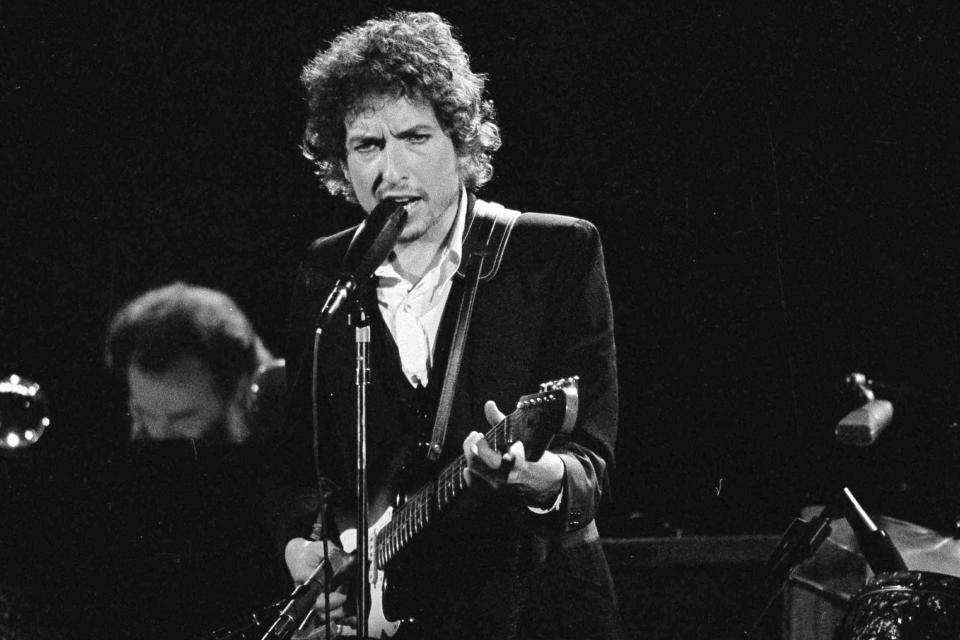 "FILE - Musician Bob Dylan performs with The Band at the Forum in Los Angeles on Feb. 15, 1974. Transcripts of lost 1971 Dylan interviews with the late American blues artist Tony Glover and letters the two exchanged reveal that Dylan changed his name from Robert Zimmerman because he worried about anti-Semitism, and that he wrote ""Lay Lady Lay"" for actress Barbra Streisand. The items are among a trove of Dylan archives being auctioned in November 2020 by Boston-based R.R. Auction. (AP Photo/Jeff Robbins, File)"