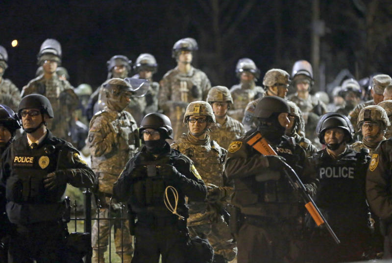 FILE - In this Friday, Nov. 28, 2014, file photo, police and Missouri National Guardsmen stand guard as protesters gather in front of the Ferguson Police Department, in Ferguson, Mo. In Ferguson, police drew heavy criticism for their militarized response to protests after unarmed 18-year-old Michael Brown, who was black, was fatally shot by white officer Darren Wilson, who was not charged and later resigned. Police have given demonstrators in the latest St. Louis protests a wide berth, applying a lesson learned in nearby Ferguson to offer protesters ample room to have their say, at least until trouble starts. (AP Photo/Jeff Roberson, File)