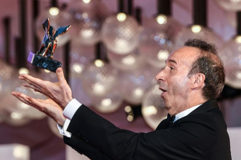 Benigni showed off his juggling skills with his lifetime achievement award. (AFP/Filippo MONTEFORTE)
