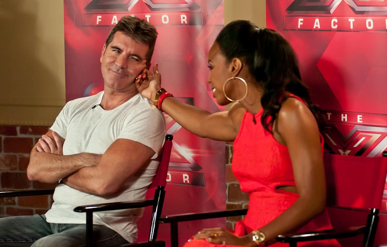 "Simon Cowell and Kelly Rowland attend the ""The X Factor"" Judges press conference at Nassau Veterans Memorial Coliseum on June 20, 2013 in Uniondale, New York."