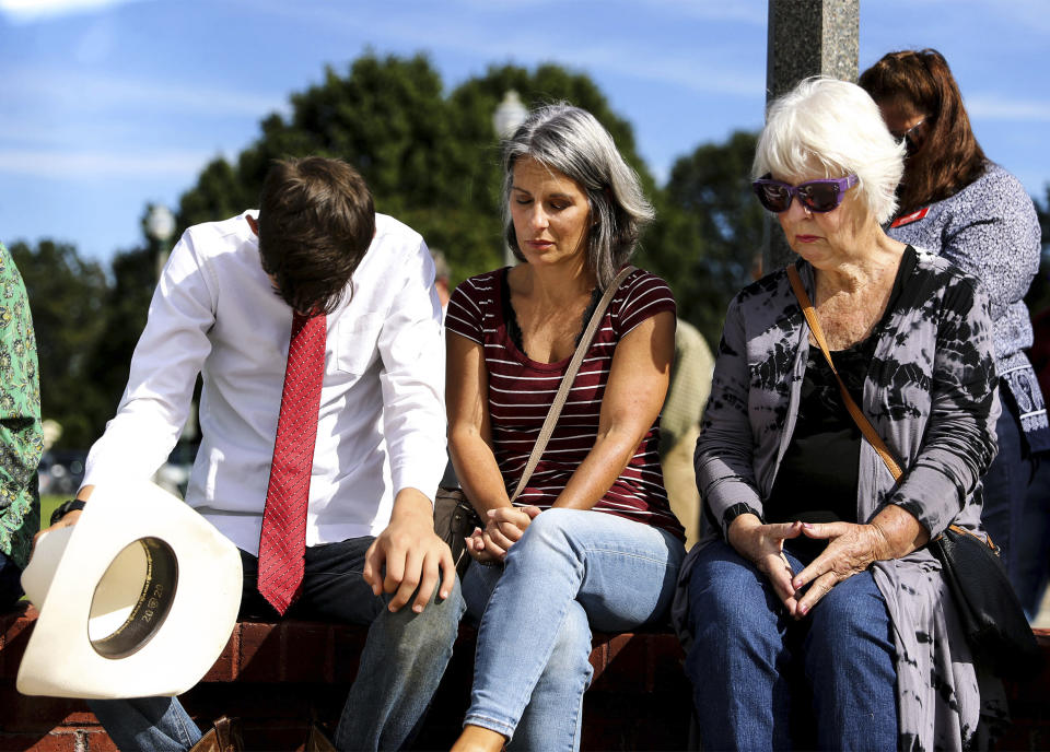 Noah Gervase, Maria Gervase and Peggy Harwell bow their heads in prayer during a vigil at Collierville Town Hall, Friday, Sept. 24, 2021, in Collierville, Tenn., for the victims of the Kroger store shooting. (Patrick Lantrip/Daily Memphian via AP)