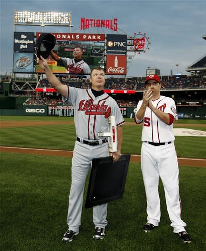 Atlanta Braves third baseman Chipper Jones acknowledges the crowd with Washington Nationals first baseman Adam LaRoche applauding during a ceremony to honor Jones before a baseball game at Nationals Park, Wednesday, Aug. 22, 2012, in Washington. (AP Photo/Alex Brandon)