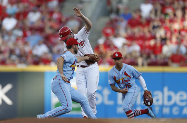 Cincinnati Reds' Jesse Winker, center, is out on a double play ball off the bat of Joey Votto as St. Louis Cardinals shortstop Paul DeJong, left, makes the tag during the first inning of a baseball game, Saturday, July 20, 2019, in Cincinnati. (AP Photo/Gary Landers)