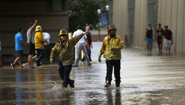 Firefighters shout directions as they wade through water near Pauley Pavillion on the University of California, Los Angeles campus, which is flooded after a broken 30-inch water main gushed water onto Sunset Boulevard, in the Westwood section of Los Angeles July 29, 2014. The geyser from the 100-year-old water main flooded parts of the UCLA campus and stranded motorists on surrounding streets. REUTERS/Danny Moloshok (UNITED STATES - Tags: DISASTER ENVIRONMENT SOCIETY)