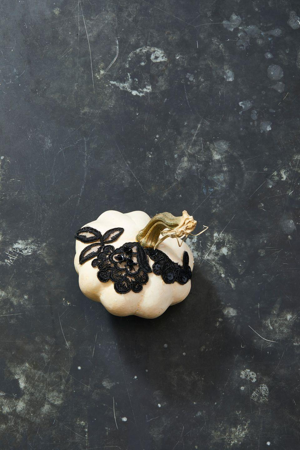 <p>Fabric trimmings and appliqués from craft stores make perfect, easy decoration for your pumpkins! Paint the pumpkin to match your home's aesthetic, then use a hot glue gun to attach the trimmings. </p>