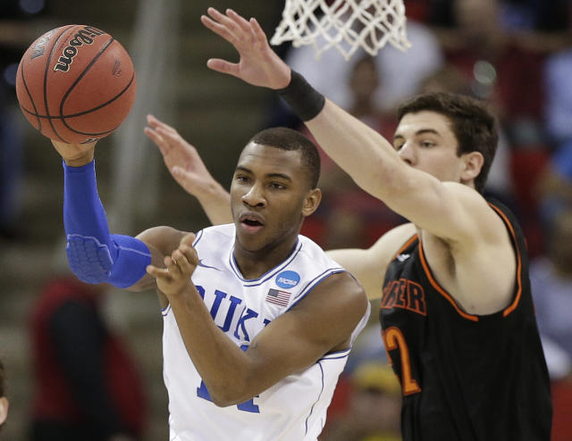 Duke guard Rasheed Sulaimon (14) passes a rebounded ball against Mercer forward Daniel Coursey (52) during the first half of an NCAA college basketball second-round game, Friday, March 21, 2014, in Raleigh, N.C. (AP Photo/Chuck Burton)