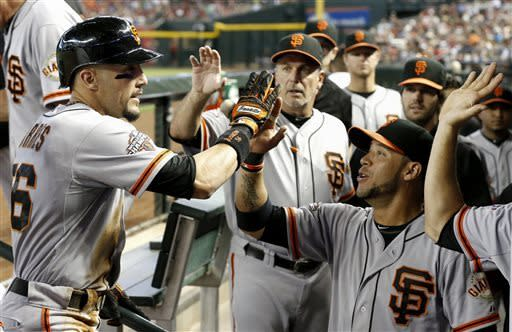 San Francisco Giants' Andres Torres, left, gets high-fives from teammate Gregor Blanco, right, and bench coach Ron Wotus after Torres scores a run against the Arizona Diamondbacks during the first inning in a baseball game on Sunday, June 9, 2013, in Phoenix. (AP Photo/Ross D. Franklin)