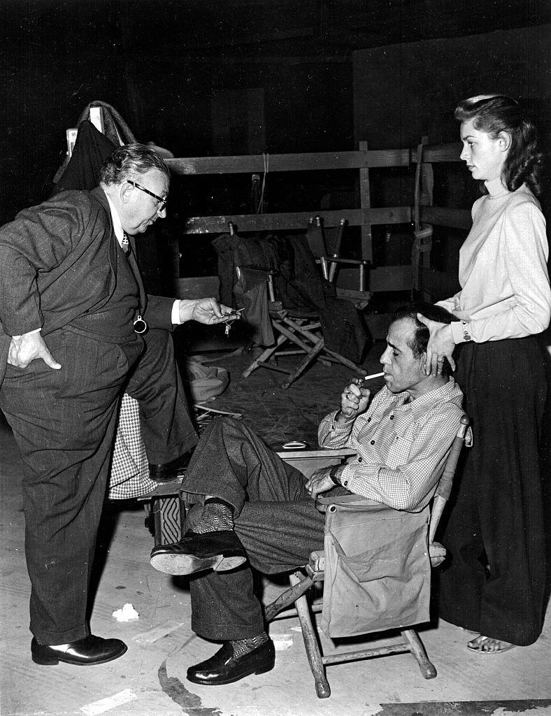 <p>Lauren Bacall massages Humphrey Bogart's head as he lights a cigarette and speaks to the director on the set of Dark Passage. The two stars were married after meeting on the set of To Have and Have Not.</p>