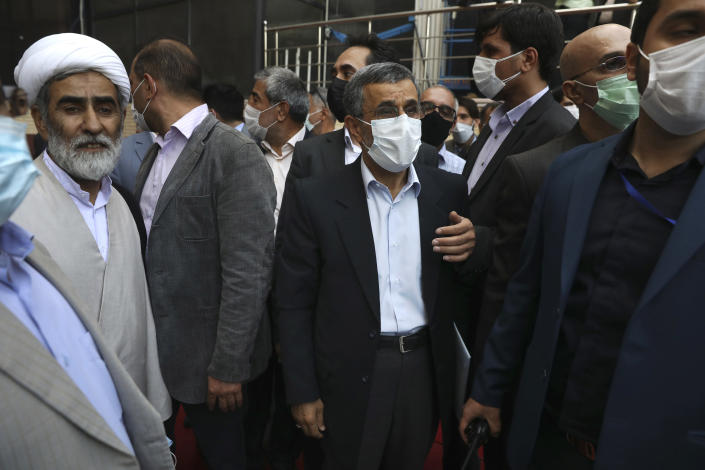 Escorted by his bodyguards and allies, former President Mahmoud Ahmadinejad, center, arrives at the Interior Ministry to register his name as a candidate for the June 18, presidential elections at elections in Tehran, Iran, Wednesday, May 12, 2021. The country's former firebrand president will run again for office in upcoming elections in June. The Holocaust-denying Ahmadinejad has previously been banned from running for the presidency by Supreme Leader Ayatollah Ali Khamenei in 2017, although then, he registered anyway. (AP Photo/Vahid Salemi)