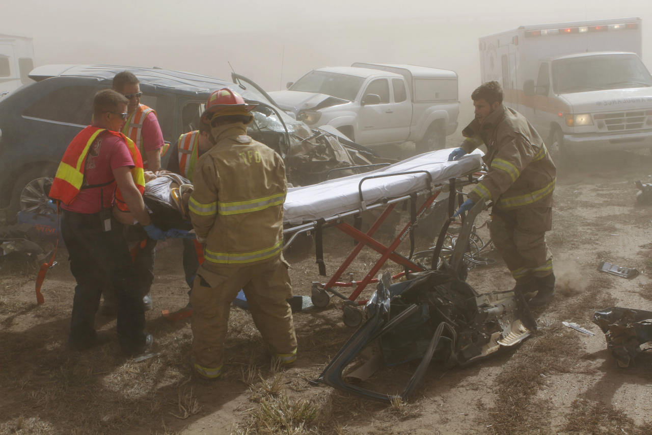 Rescue personnel from the Tonkawa Fire Department extricate a woman pinned in vehicle after it was involved in an accident on Interstate 35 near Blackwell, Okla., Thursday, Oct. 18, 2012 A massive dust storm swirling reddish-brown clouds over northern Oklahoma triggered a multi-vehicle accident, forcing police to shut down the heavily traveled roadway amid near blackout conditions. The highway patrol said the dust storm caused a multi-car accident, and local police said nearly three dozen cars and tractor-trailers were involved. Blackwell Police Chief Fred LeValley said nine people were injured, but there were no fatalities. (AP Photo/The Ponca City News, Rolf Clements) MANDATORY CREDIT