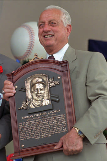FILE - Tommy Lasorda poses with his Hall of Fame plaque after his induction in Cooperstown, N.Y., in this Aug. 3, 1997, file photo. Tommy Lasorda, the fiery Hall of Fame manager who guided the Los Angeles Dodgers to two World Series titles and later became an ambassador for the sport he loved during his 71 years with the franchise, has died. He was 93. The Dodgers said Friday, Jan. 8, 2021, that he had a heart attack at his home in Fullerton, California. Resuscitation attempts were made on the way to a hospital, where he was pronounced dead shortly before 11 p.m. Thursday. (AP Photo/ Dave Jennings, File)
