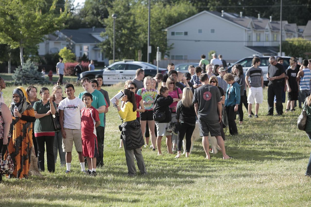 Students and family line up to receive personal property at the north gym of Reynolds Middle School on Tuesday evening, June 10, 2014, in Troutdale, Ore. A teen gunman armed with a rifle shot and killed a 14-year-old student Tuesday and injured a teacher before he likely killed himself at a high school in a quiet Columbia River town in Oregon, authorities said. (AP Photo/The Oregonian, Michael Lloyd)