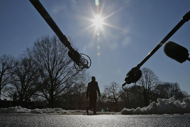 Microphones are extended towards President Barack Obama as he walks on the South Lawn of the White House in Washington, Friday, Feb. 14, 2014, before boarding the Marine One helicopter to travel to the Democratic House members retreat in Cambridge, Md. (AP Photo/Charles Dharapak)