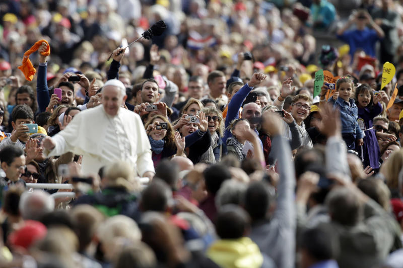 Faitfhful cheer and take photographs of Pope Francis during the weekly general audience in St. Peter's Square, at the Vatican, Wednesday, Oct. 9, 2013. (AP Photo/Gregorio Borgia)