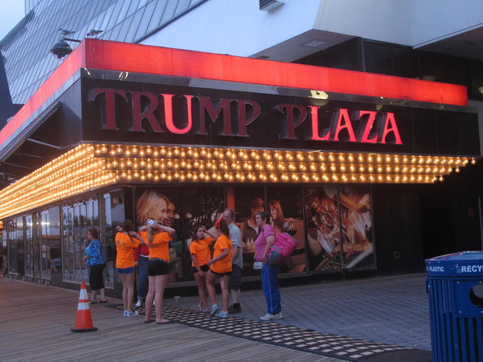 This July 24, 2014 photo shows a partially burnt-out sign on the exterior of the Trump Plaza casino in Atlantic City, N.J. On Jan. 18, 2021, an auction house soliciting bids for the right to press the button to implode the shuttered casino stopped the effort after receiving a cease-and-desist letter from billionaire Carl Icahn, who owns the property. Icahn says the auction would have promoted something her considered to be a safety risk, and said he will replace the $175,000 that would have gone to the Boys Girls Club of Atlantic City. (AP Photo/Wayne Parry)