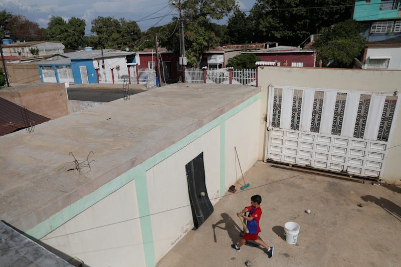 Baseball little league player Santiago Lopez, 10, practices baseball during an electricity cut at his house in Maracaibo, Venezuela. (Photo: Manaure Quintero/Reuters)