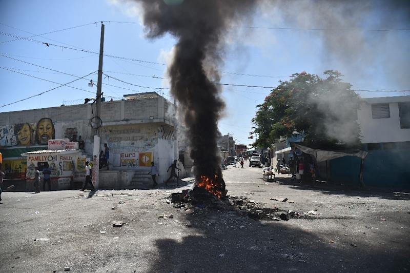 Haitian people walk a street before a smouldering barricade in central Port-au-Prince, July 9, 2018, following two days of rioting triggered by a government attempt to raise fuel prices