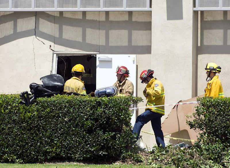 Authorities respond to the scene where a car crashed into the Tutoring Club in Fountain Valley, Calif., on Monday, Aug. 19, 2013. Police say a 76-year-old man drove his car into the tutoring club, injuring five people, including two who were trapped underneath the vehicle. (AP Photo/The Orange County Register, Sam Gangwer)