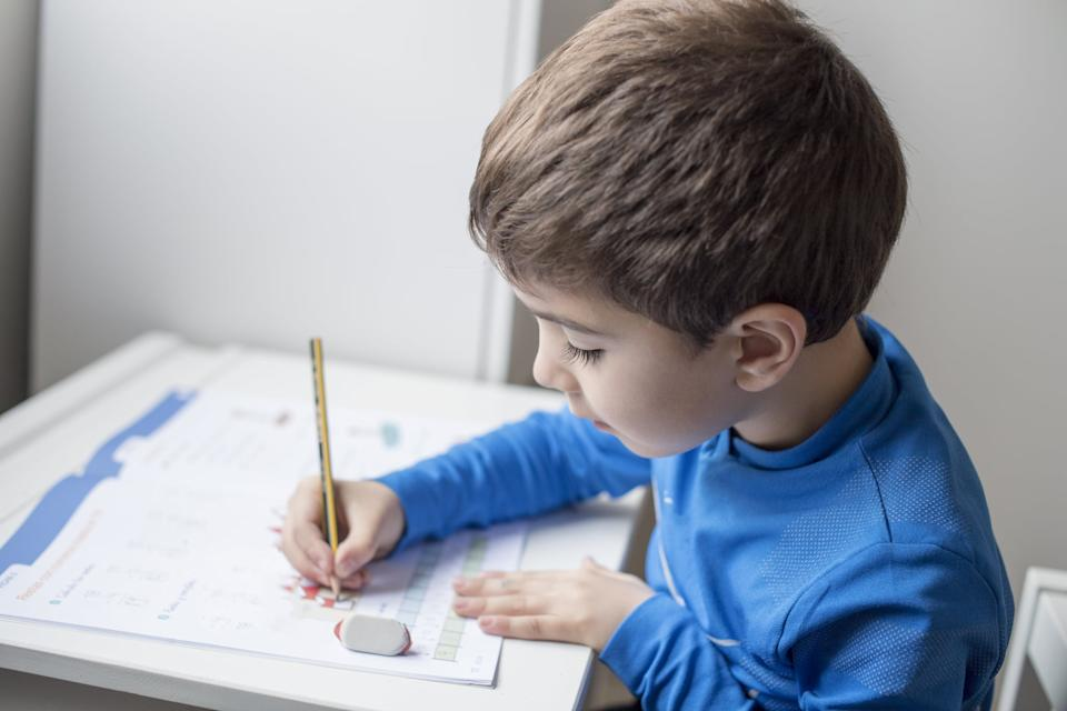 Boy sitting at table doing homework with pencil