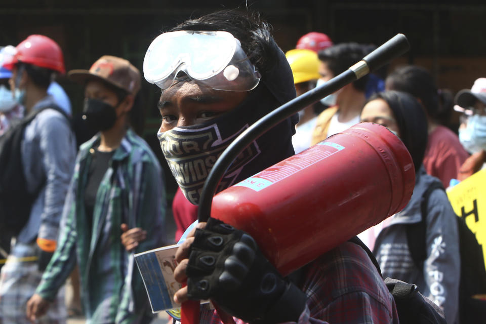 A protester carries a fire extinguish during an anti-coup demonstration in Mandalay, Myanmar, Saturday, March 6, 2021. The U.N. special envoy for Myanmar on Friday called for urgent Security Council action, saying about 50 peaceful protesters were killed and scores were injured in the military's worst crackdowns this week. (AP Photo)