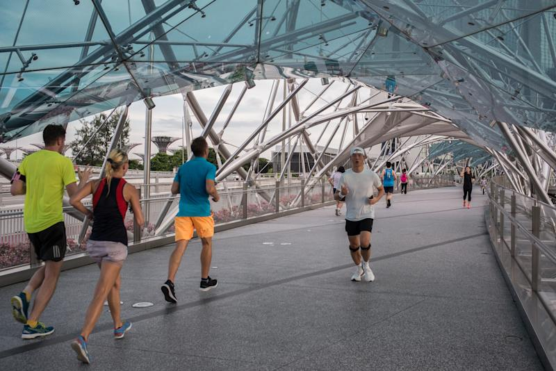 SINGAPORE - 2020/05/16: People jog along the helix bridge, a bridge that connects Marina Center to Marina South, during the Coronavirus (COVID-19) crisis. Singapore has so far confirmed 27,356 coronavirus cases, 22 deaths and 8,342 recovered, based on the latest update by the country's Ministry of Health. (Photo by Maverick Asio/SOPA Images/LightRocket via Getty Images)