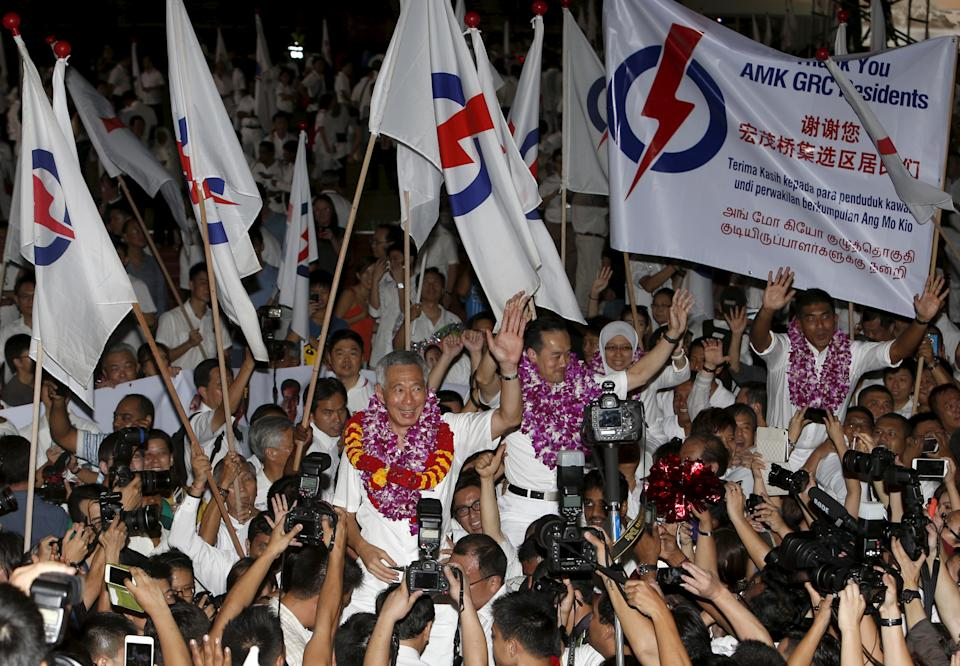 Singapore's Prime Minister and Secretary-General of the People's Action Party Lee Hsien Loong (C) celebrates with supporters after the general election results at a stadium in Singapore September 12, 2015.  Singapore voted on Friday in its most hotly contested general election with the outcome expected to test the long-ruling People's Action Party's (PAP) dominance of politics even though it is bound to win. REUTERS/Edgar Su