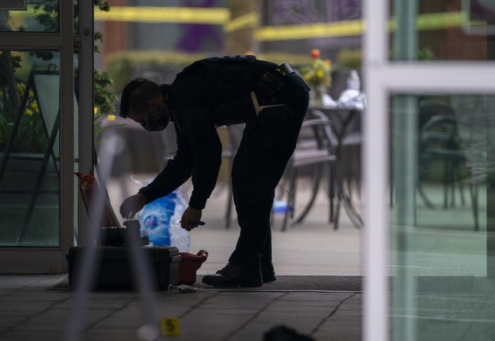 A member of the RCMP is silhouetted as he investigates the scene at the Lynn Valley Library, in North Vancouver, British Columbia Saturday, March 27, 2021. Police say multiple victims were stabbed inside and outside the library today. (Jonathan Hayward/The Canadian Press via AP)