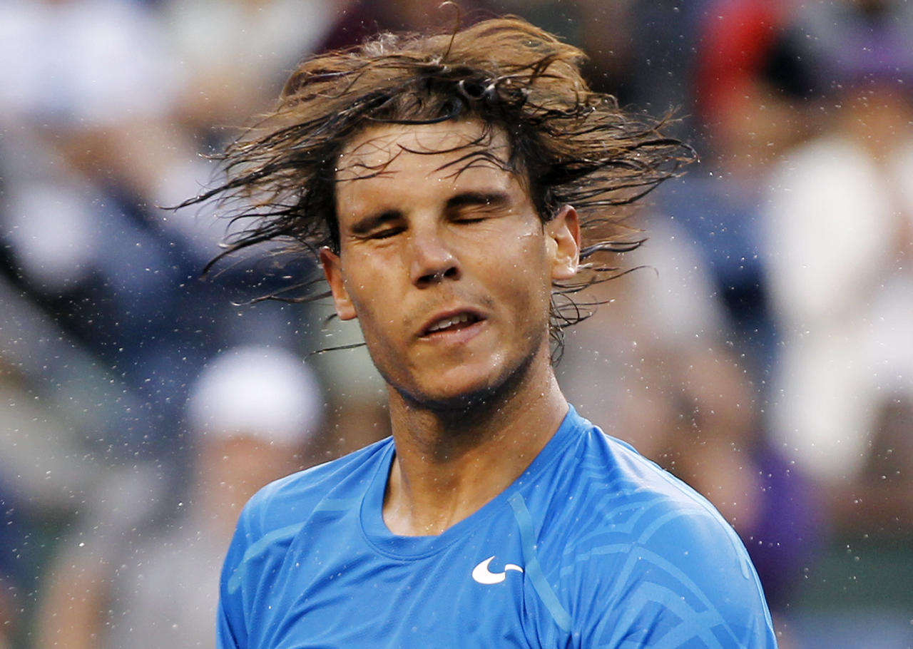 Rafael Nadal of Spain shakes the sweat off his hair after defeating compatriot Marcel Granollers in their match at the Indian Wells ATP tennis tournament in Indian Wells, California, March 13, 2012. REUTERS/Danny Moloshok (UNITED STATES - Tags: SPORT TENNIS TPX IMAGES OF THE DAY)