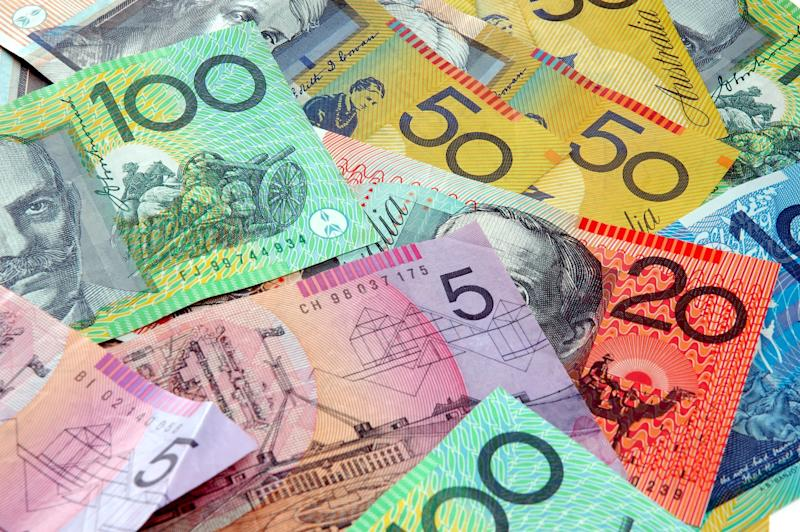 Australian notes scattered on a table. Covid-19 hardship payment concept.