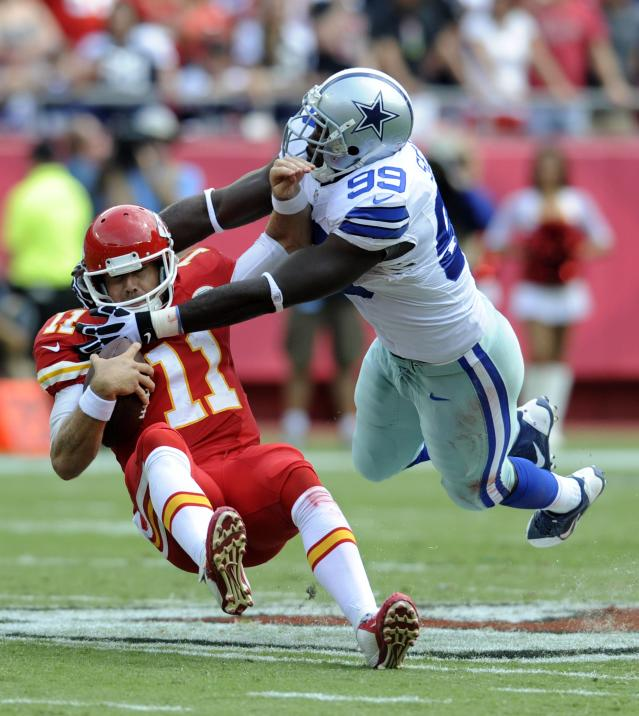 Kansas City Chiefs quarterback Alex Smith is brought down by Dallas Cowboys defensive end George Selvie during the first half of their NFL football game in Kansas City, Missouri September 15, 2013. REUTERS/Dave Kaup (UNITED STATES - Tags: SPORT FOOTBALL)