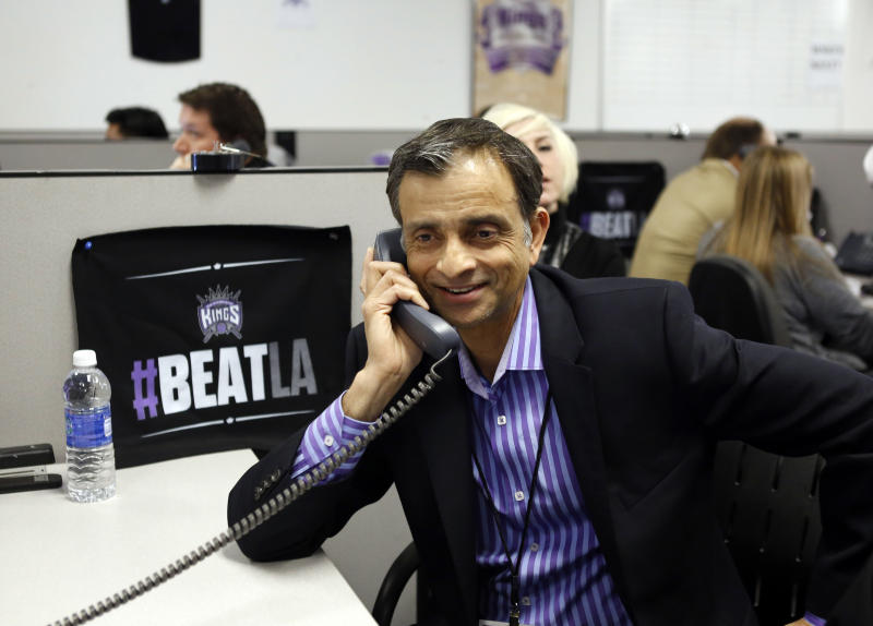 Vivek Ranadive, the new majority owner of the Sacramento Kings NBA basketball team smiles as a season ticket holder he called pledged to renew their seats, during a visit to the team's offices at Sleep Train Arena in Sacramento, Calif., Thursday, May 23, 2013. Ranadive joined employees in calling season ticket holders to encourage them to renew their tickets for next season. (AP Photo/Rich Pedroncelli)