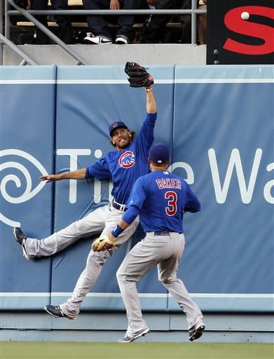Chicago Cubs center fielder Joe Mather, left, and right fielder Jeff Baker can't reach a home run by Los Angeles Dodgers' Matt Kemp during the fourth inning of a baseball game at Dodger Stadium in Los Angeles on Saturday, Aug. 4, 2012. (AP Photo/Reed Saxon)