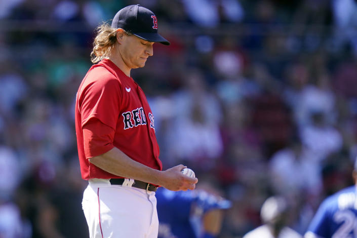 Boston Red Sox starting pitcher Garrett Richards looks down at a fresh baseball after giving up a two-run home run to Toronto Blue Jays' Randal Grichuk in the fourth inning of a baseball game at Fenway Park, Wednesday, July 28, 2021, in Boston. (AP Photo/Charles Krupa)