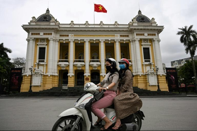 Women wearing face masks ride past the Opera House in Hanoi on April 23, 2020, as Vietnam eased its nationwide social isolation effort to prevent the spread of the COVID-19 novel coronavirus. Vietnam eased social distancing measures on April 23, with experts pointing to a decisive response involving mass quarantines and expansive contact tracing for the apparent success in containing the coronavirus. (AFP Photo/Manan VATSYAYANA)