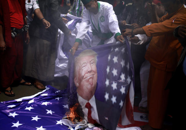 <p>Protesters burn a poster of U.S. President Donald Trump during a rally outside U.S. Embassy in Jakarta, Indonesia, Monday, Dec. 11, 2017. Hundreds of people staged the protest in the Indonesian capital of Jakarta to denounce Trump's decision to recognize Jerusalem as Israel's capital. (AP Photo/Dita Alangkara) </p>