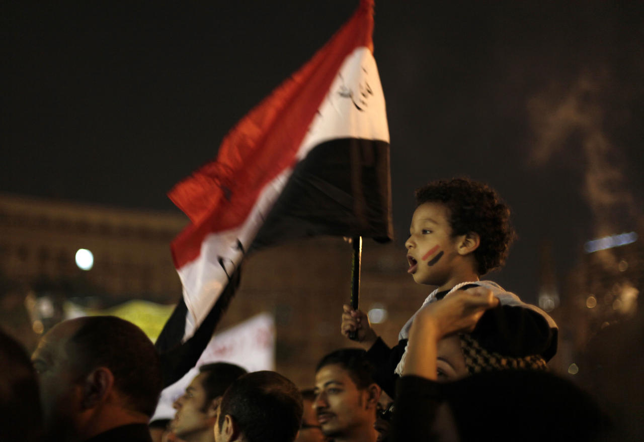 A young Egyptian boy waves a national flag from his mother's shoulders as protesters chant slogans in Tahrir Square in Cairo, Egypt, Tuesday, Dec. 4, 2012. A protest by tens of thousands of Egyptians outside the presidential palace in Cairo turned violent on Tuesday as tensions grew over Islamist President Mohammed Morsi's seizure of nearly unrestricted powers Thousands of protesters also gathered in Cairo's downtown Tahrir Square, miles away from the palace, to join several hundred who have been camping out there for nearly two weeks. (AP Photo/Maya Alleruzzo)